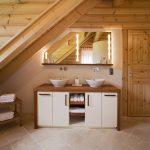 Naturverbundenheit Zuhause leben Natürlich-moderne Badezimmereinrichtung im echten Holz-Blockhaus nach kanadischer Art. In die Dusche geht es durch einen kurzen Schneckengang, hinter dem Spiegelschrank mit integrierten Leuchtpaneelen warten Pflege- und Badartikel auf ihren Einsatz